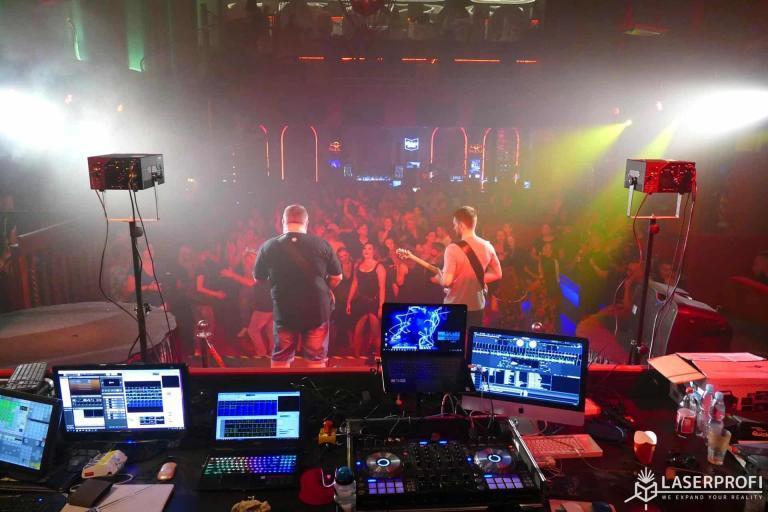 Koncert w klubie dyskotekowym z pokazem laserow - widok z za stolu djskiego
